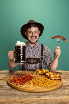 Happy smiling man dressed in traditional austrian or bavarian costume sitting at table with festive food and beer isolated over red background