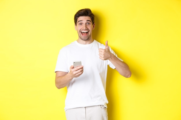 Happy smiling man holding smartphone, showing thumb up in approval, recommend something online, standing over yellow background.