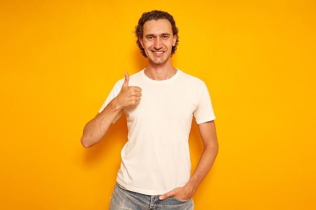 黄色の背景に白いtシャツとカジュアルな服を着て幸せな笑顔の男はいいね!