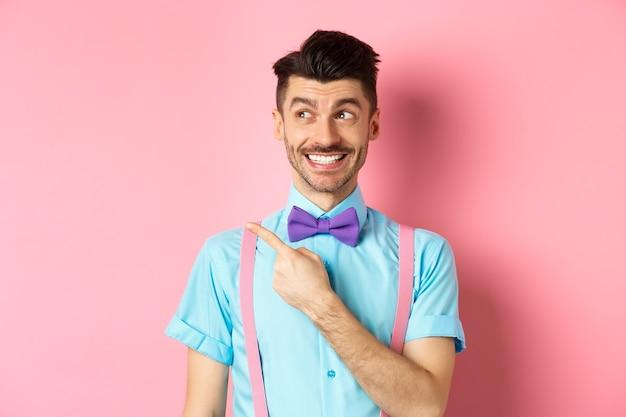 Счастливый улыбающийся человек в забавном наряде и галстуке-бабочке, указывая пальцем влево и глядя на логотип, показывает рекламу на розовом.
