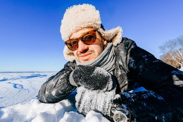屋外の雪の中でポーズをとってサングラスで幸せな笑顔の男