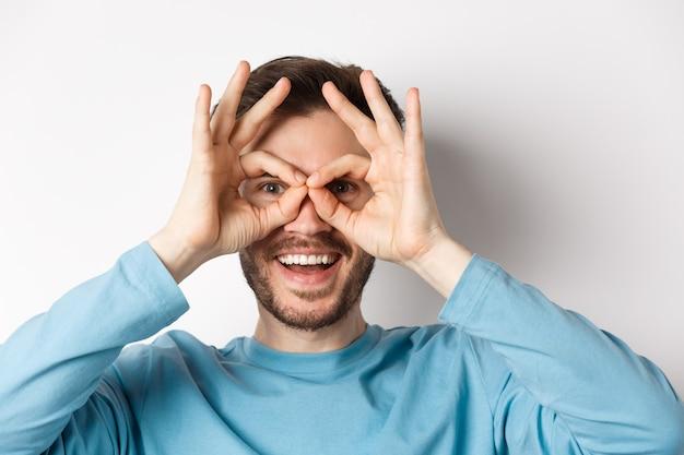 Uomo sorridente felice che guarda attraverso il binocolo a mano con il viso stupito, controllando l'offerta promozionale, in piedi su sfondo bianco.