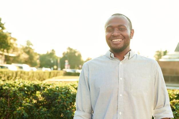 幸せな笑顔の男屋外。公園で笑顔の若いアフリカ人の屋外の肖像画。