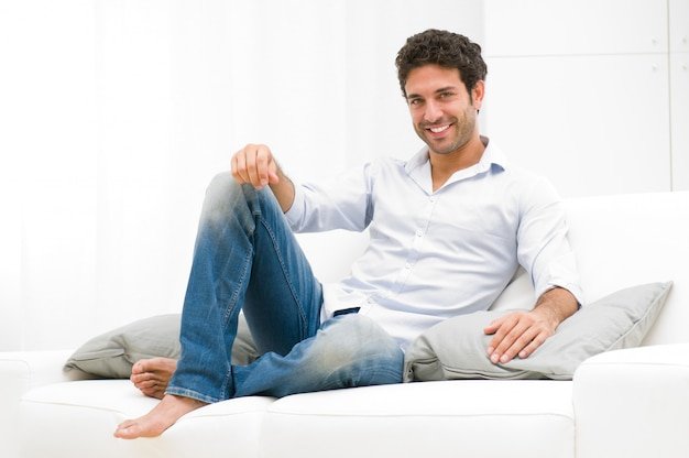 Happy smiling man relaxing and sitting on sofa at home