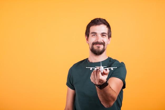 旅行のコンセプト画像でカメラにおもちゃの飛行機を見せて幸せな笑顔の男。観光と自由