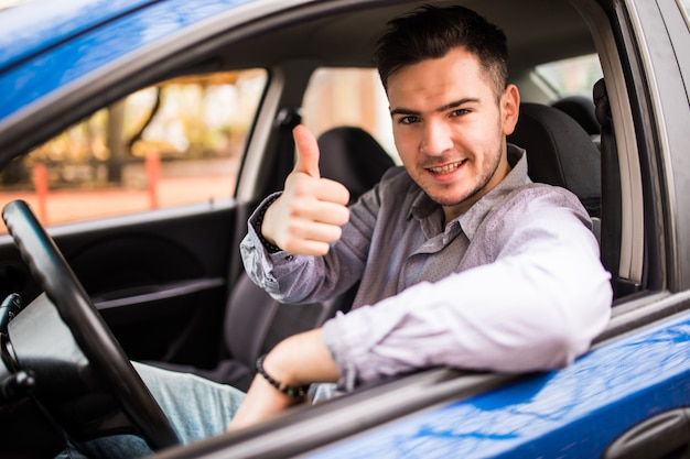 Happy smiling man sitting inside car showing thumbs up. handsome guy excited about his new vehicle. positive face expression
