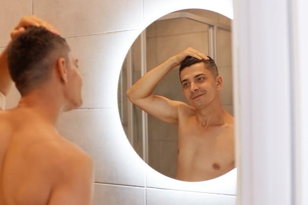 裸の上半身で立って、鏡の中の彼の反射を見て笑顔を見て、朝シャワーを浴びた後、バスルームでポーズをとって幸せな笑顔の男。