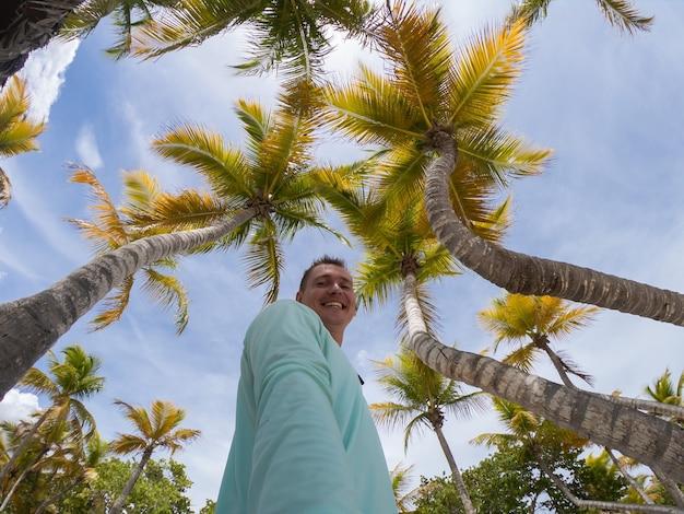 Счастливый улыбающийся человек, делающий селфи на пляже и пальмах. концепция отпуска и путешествий.