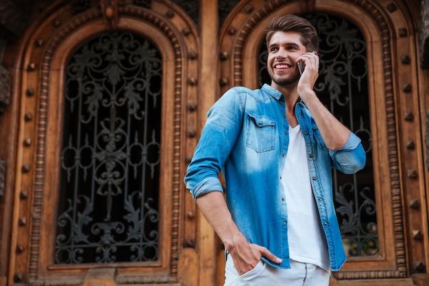 Счастливый улыбающийся человек разговаривает по мобильному телефону, стоя перед деревянной дверью на улице