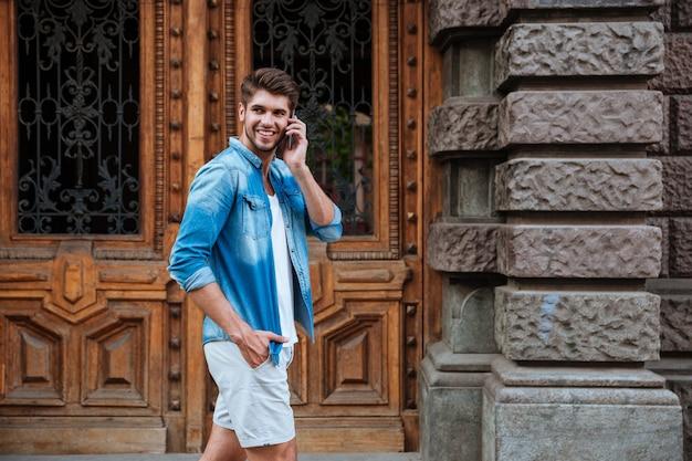 Счастливый улыбающийся человек разговаривает по мобильному телефону во время прогулки по улице