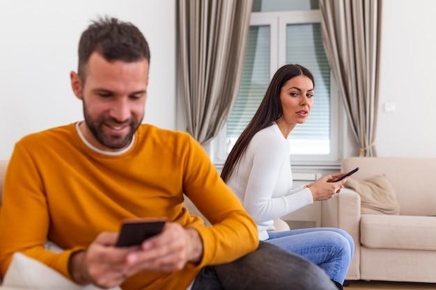 Счастливый улыбающийся мужчина повернулся спиной к жене, читая сообщение по телефону от своего любовника