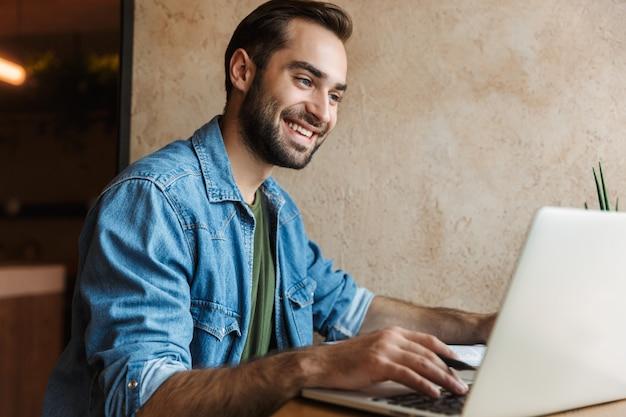 Счастливый улыбающийся человек в джинсовой рубашке смотрит на ноутбук во время работы в кафе в помещении