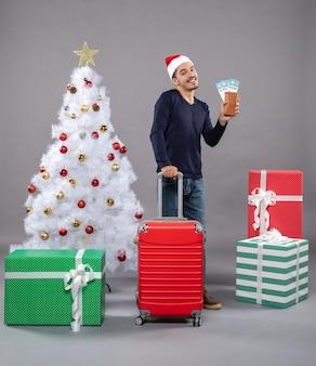 Uomo sorridente felice con la sua valigia e biglietti di viaggio su grigio