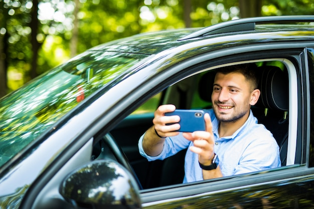 Happy smiling man with smartphone driving in car and taking photo of situation outdoors