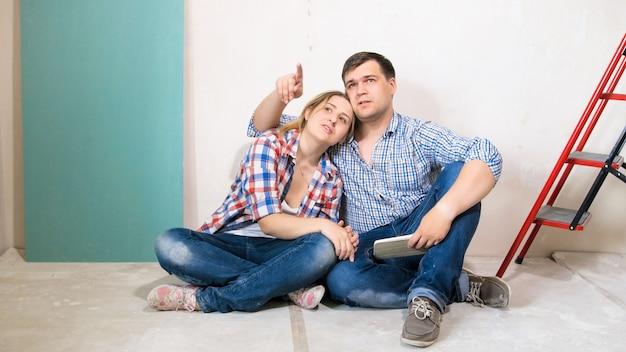 Счастливый улыбающийся мужчина с женой, выбирая цвет краски для стен в их новом доме под ремонтом.