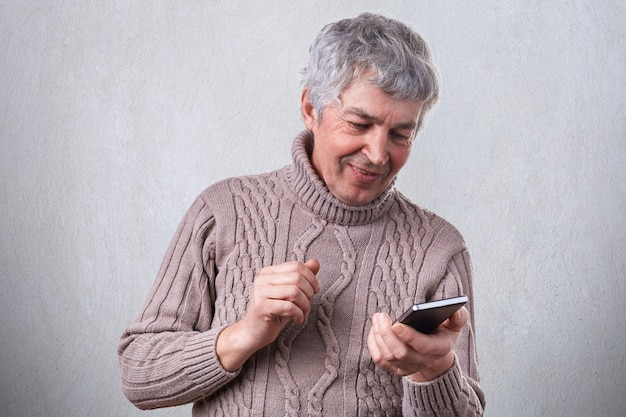 A happy smiling mature man holding his smartphone in hands being pleased to receive message from his son