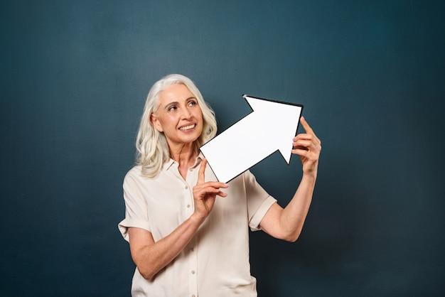 행복 한 미소 성숙한 늙은 여자 화살표를 들고입니다.