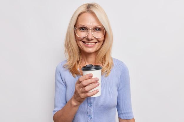 Счастливая улыбающаяся зрелая женщина со светлыми волосами покупает напиток с кофеином в кафе, держит одноразовую чашку кофе, носит прозрачные очки, повседневный синий джемпер, изолированный над белой стеной. образ жизни.
