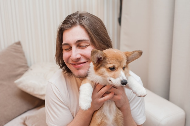 Happy smiling men cuddles himself with a puppy corgi.
