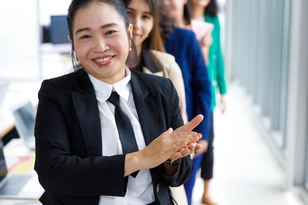 フォーマルなビジネススーツの幸せな笑顔の中年女性マネージャーは、ぼやけた背景の前の女性の同僚の新しい昇進の同僚への褒め言葉の祝福の暖かい挨拶を示して拍手喝采します。