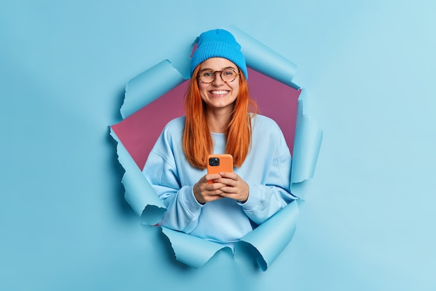 Happy smiling millennial girl with red hair holds modern cellular enjoys texting in social media uses mobile network services wears blue jumper and hat.