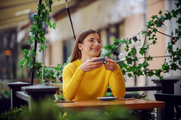 Happy smiling millennial girl in yellow sweater sitting on terrace of cafe and enjoying coffee