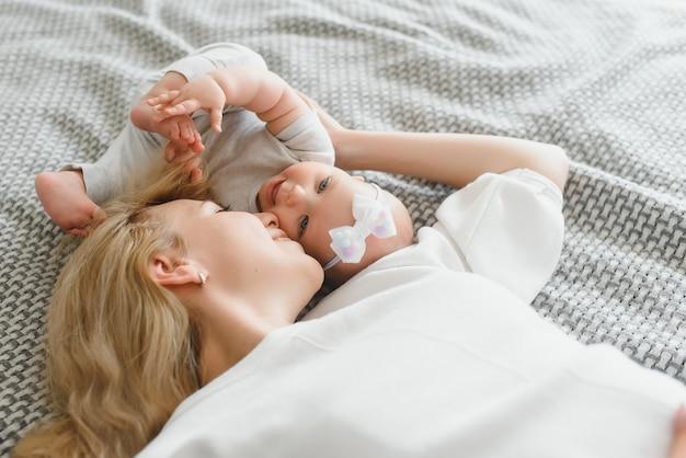 집에서 침대에 누워 행복 웃는 엄마와 아기, 상위 뷰