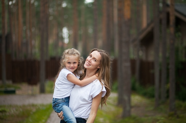 幸せな笑顔の母と抱き締めてかわいい感情的な小さな娘