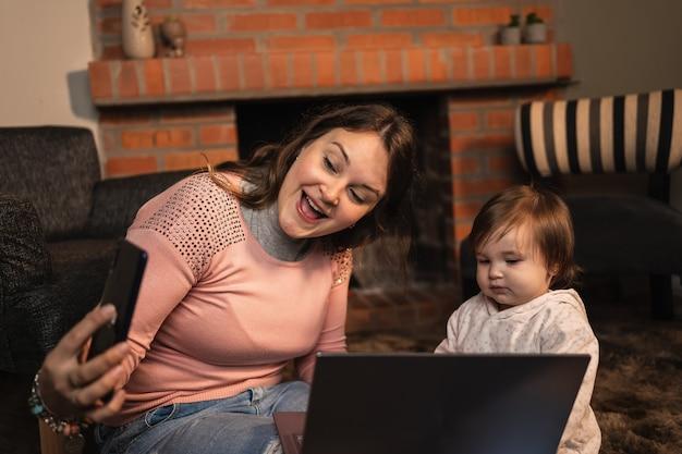 Счастливая улыбающаяся мать и милая маленькая дочь, делающая селфи на смартфоне.