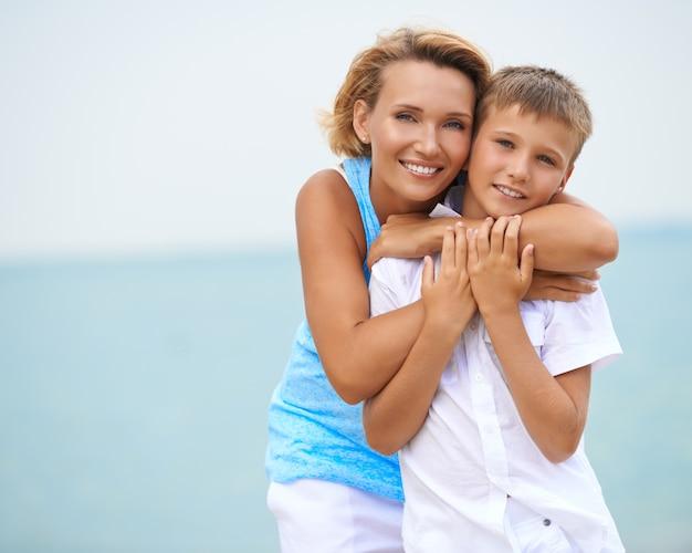 Счастливые улыбающиеся мать и сын, весело проводящие время на пляже.