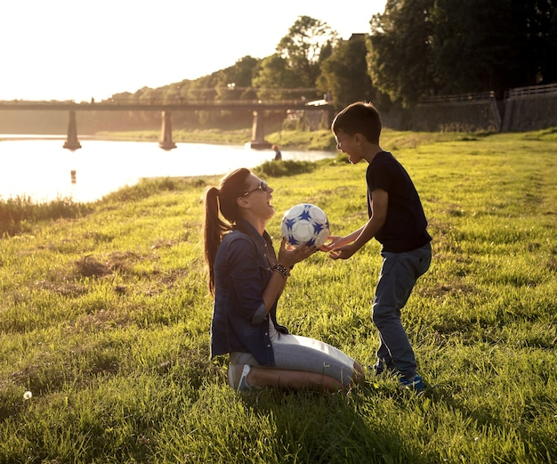 야외에서 축구공을 가지고 노는 행복한 미소 짓는 어머니와 아들들. 여름 햇살 말