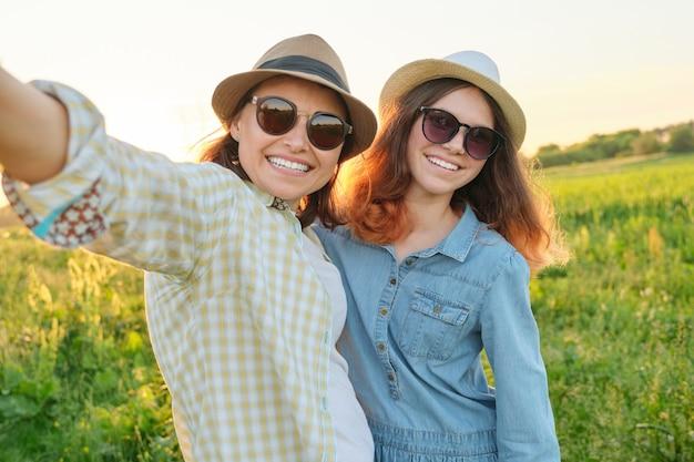 행복 한 미소 어머니와 selfie 사진을 복용하는 십 대 딸. 화창한 여름 날에 풀밭에서 걷는 여성
