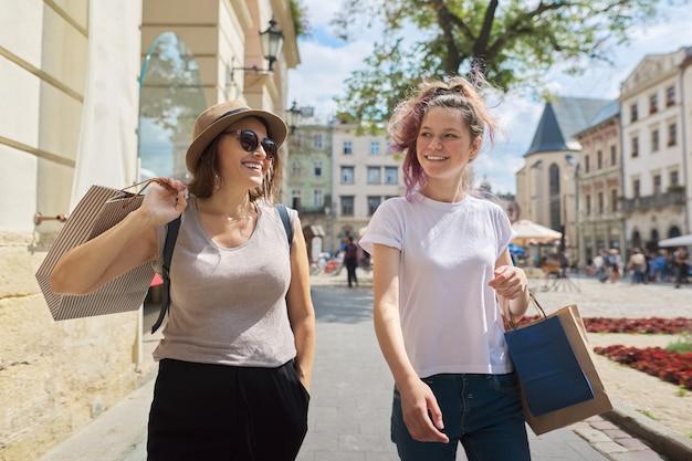 Счастливая улыбающаяся мать и дочь-подросток гуляют вместе с хозяйственными сумками
