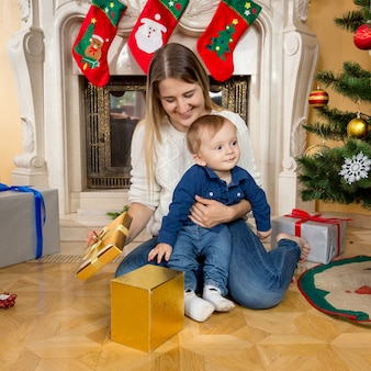 Happy smiling mother and baby on floor looking at christmas gifts
