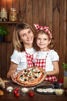Happy smiling mother and daughter with cooked pizza