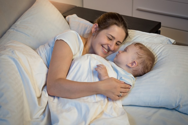 Happy smiling mother embracing her baby in bed at night