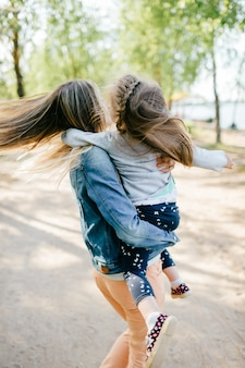 Happy smiling mother have fun with  her lovely little daughter outdoor