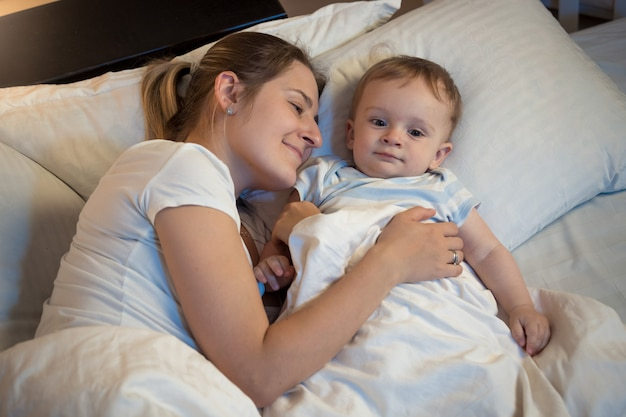Happy smiling mother hugging her little baby in bed at night