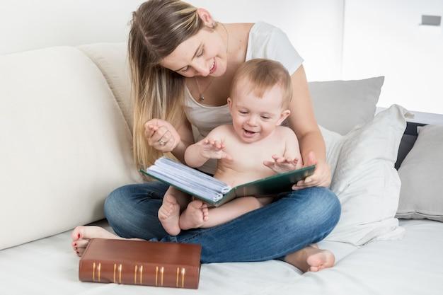 Счастливая улыбающаяся мать, глядя на фотоальбом со своим мальчиком