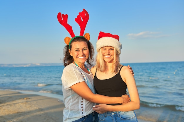 Happy smiling mother and teenage daughter in santa claus hat on the beach