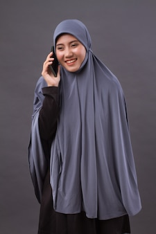 Happy smiling muslim woman using smartphone call, wireless internet device