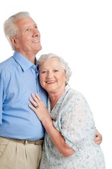 Счастливая улыбающаяся старая пара, стоя вместе изолированной на белом копировальном пространстве