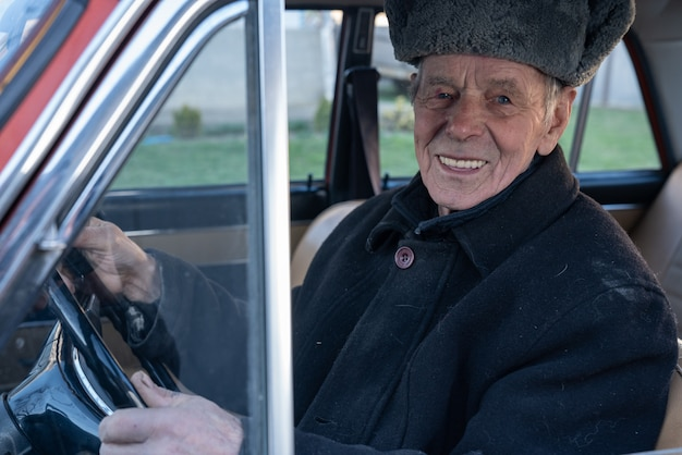 Happy smiling old man in black jacket driving retro car, holds her hands on wheel and looking at the camera