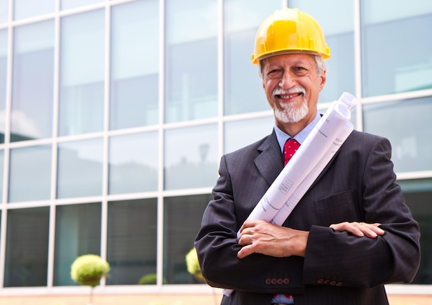 Happy, smiling older architect looking out