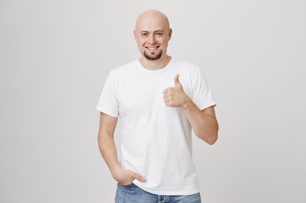 Счастливый улыбающийся, довольный лысый мужчина показывает палец вверх
