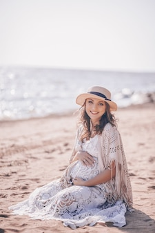 Happy smiling pregnant woman on the beach