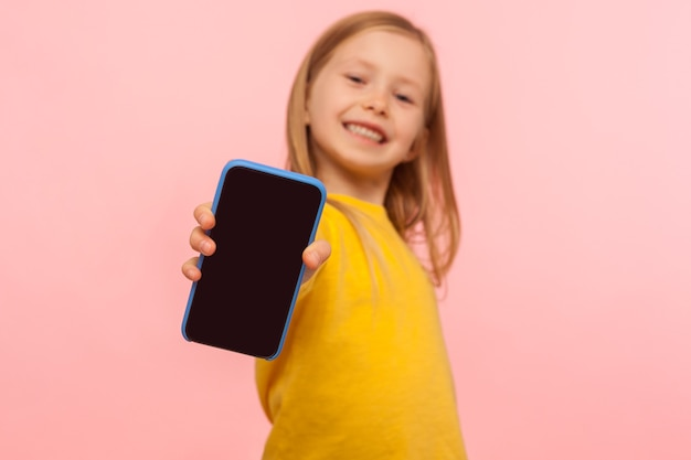 즐겁게 웃고 있는 취학 전 소녀가 즐거운 열정적인 표정으로 카메라에 휴대폰을 들고 모바일 장치 또는 어린이용 응용 프로그램을 광고하고 스마트폰에 초점을 맞춥니다. 실내 스튜디오 촬영, 절연