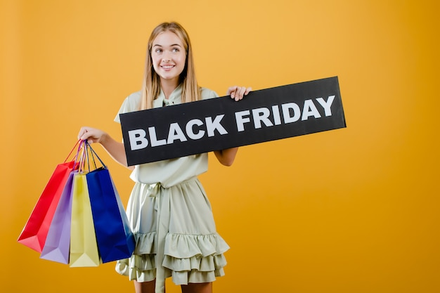Happy smiling pretty girl has black friday sign with colorful shopping bags isolated over yellow