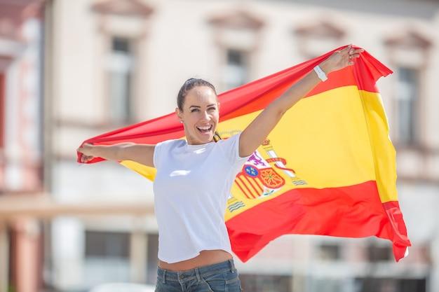 Счастливая улыбающаяся красивая девушка держит флаг испании за ее празднованием на улице.