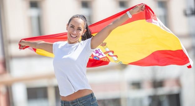 행복한 미소를 짓고 있는 예쁜 소녀는 거리에서 축하하는 그녀 뒤에 스페인 국기를 들고 있습니다.